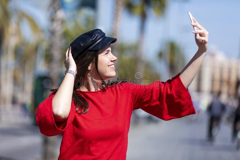 Främre sikt av härliga le tillfälliga kläder för ung kvinna som utomhus står i staden, medan ta en selfie i en ljus dag royaltyfria foton
