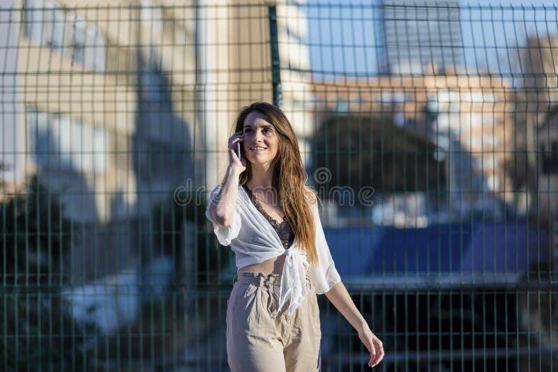 Främre sikt av härliga moderiktiga kläder för bära för ung kvinna som tillfälliga står i gatan, medan genom att använda en mobilt arkivbild