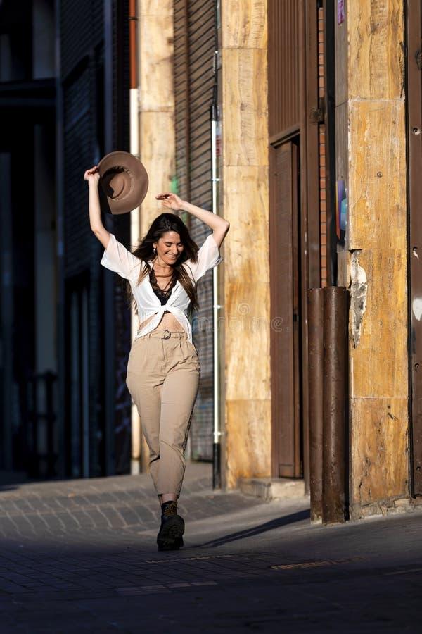 Främre sikt av härliga moderiktiga kläder för bära för ung kvinna som tillfälliga står i gatan som rymmer en hatt, medan se kamer arkivfoto