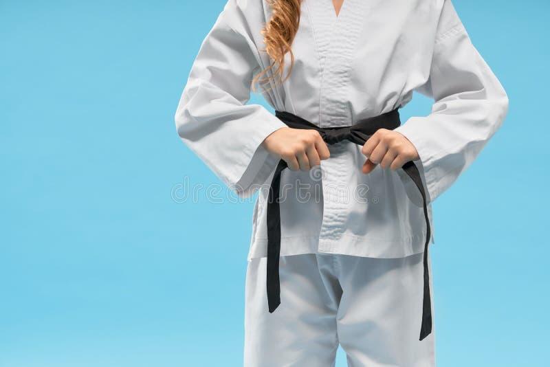 Främre sikt av kimonot på den lilla kämpen som håller det svarta bältet arkivbild