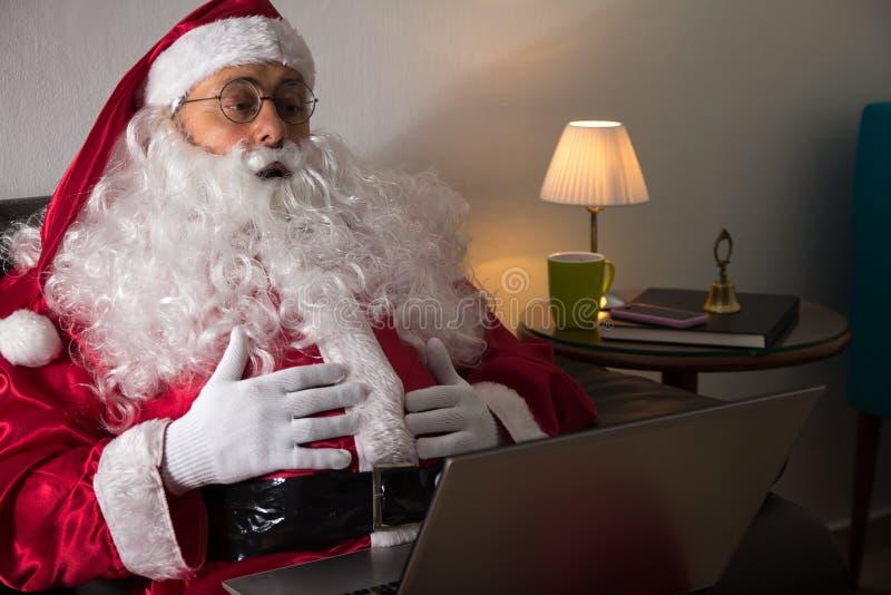 Främre sikt av Santa Claus som sitter i hemmastadd användande bärbar dator f för soffa arkivbild