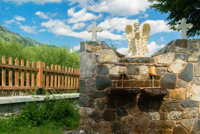Främre sikt av springbrunnen i den kyrkliga borggården royaltyfri fotografi