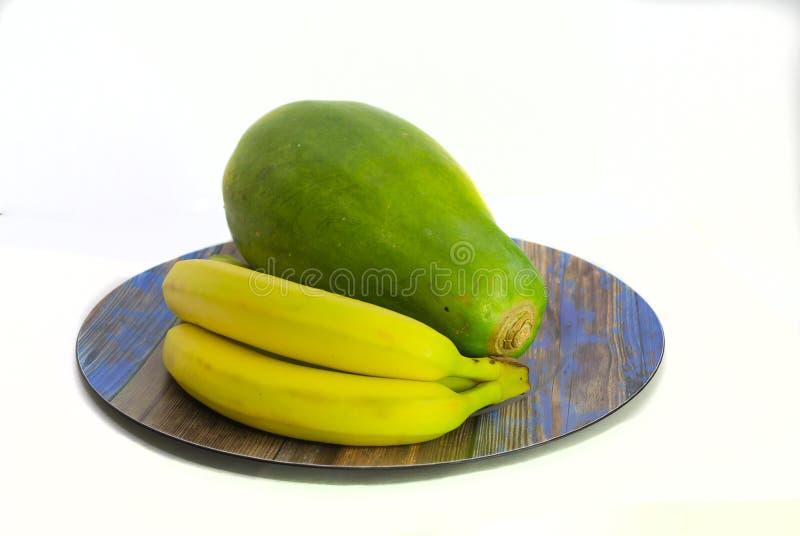 Främre sikt av två bananer och en papaya royaltyfri bild