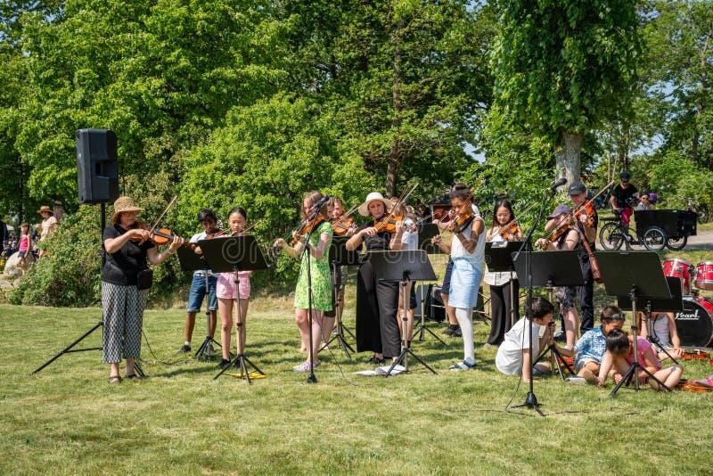 Främre sikt för sommarträdgård av vuxna människor och ungdomari en orkester med instrumentplayigklassisk musik tillsammans royaltyfria foton