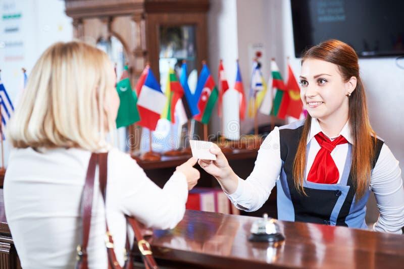 Främre skrivbord för mottagande på hotellet Arbetare och gäst arkivfoto