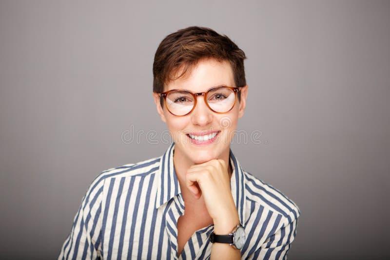 Främre stående av den härliga unga kvinnan med exponeringsglas mot grå bakgrund fotografering för bildbyråer