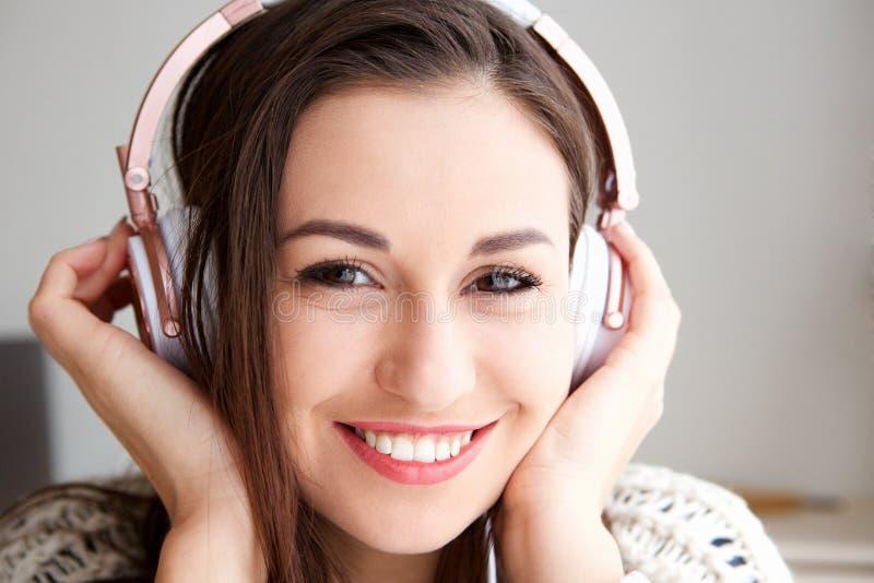 Främre stående av den lyckliga unga kvinnan som lyssnar till musik med hörlurar royaltyfri foto