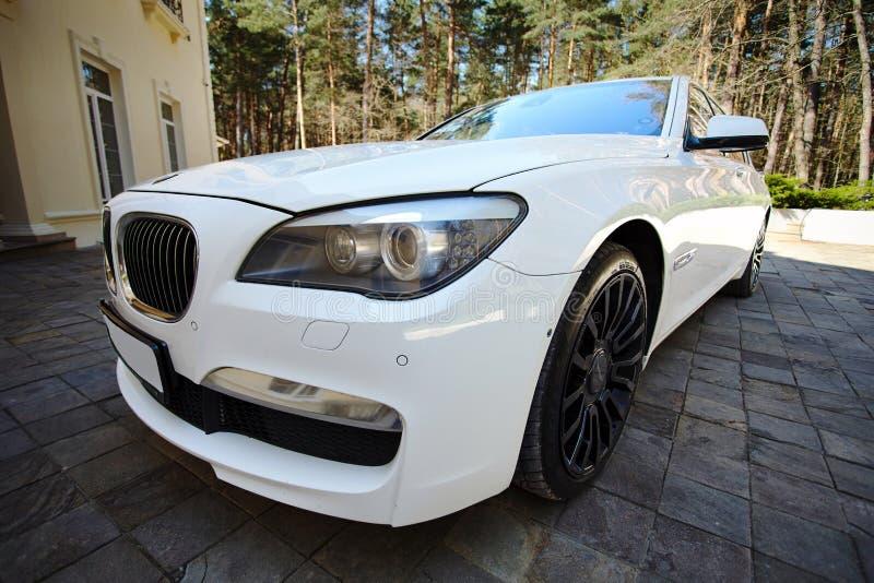 Främre trekvarts- bred sikt för modern lyxig BMW 750Li XDrive bil som parkeras på sten stenlagd parkering nära forntida hus royaltyfria foton