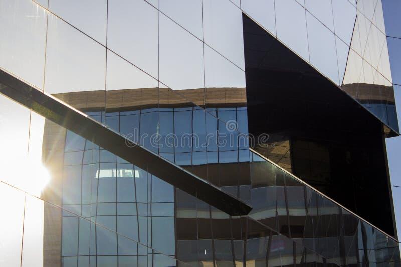 Främre väggfaçade för glass fönster av en modern kontorsbyggnad med en reflexion av en annan kontorsbyggnad som står framtill arkivfoton