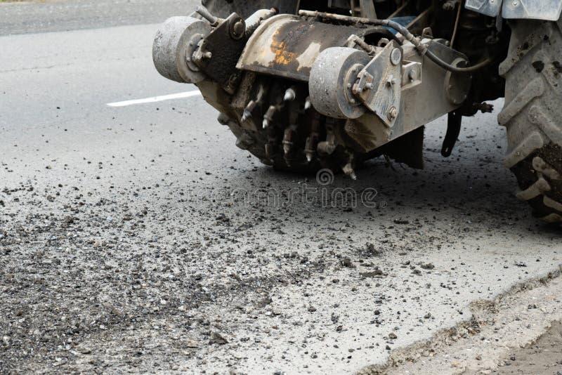 Fräsmaschine der Straße schneidet den alten Asphalt Im Bau Zerstörung der Straßendecke Der Schneider schneidet eine Schicht Aspha stockfotografie
