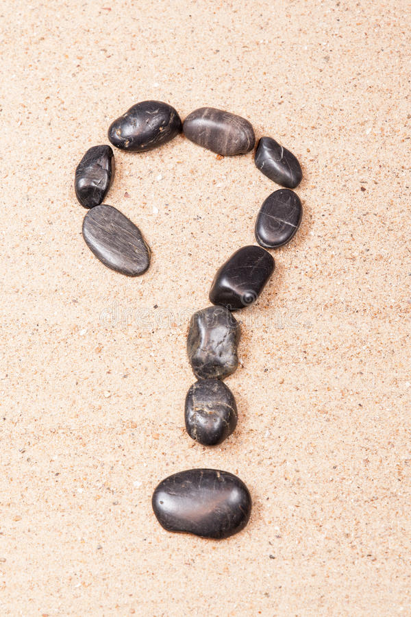 Frågefläck som dras med kiselstenar på sanden royaltyfri bild