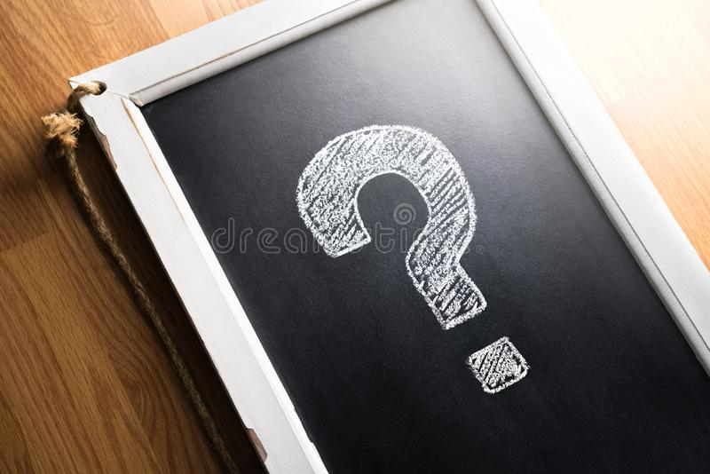 Frågefläck som dras på den svart tavlan Om oss, hjälp eller information för affär Gransknings-, röstning- eller frågesportbegrepp royaltyfri fotografi