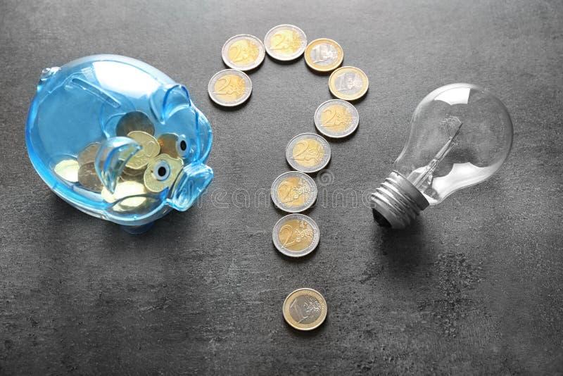 Frågefläck som göras av mynt, spargrisen och ljus kula på grå bakgrund Elektricitetsbesparingbegrepp arkivfoton
