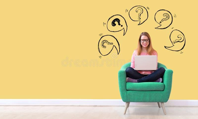 Frågefläckar med anförandebubblor med kvinnan som använder en bärbar dator arkivfoton
