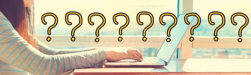 Frågefläckar med kvinnan som arbetar på en bärbar dator arkivfoton