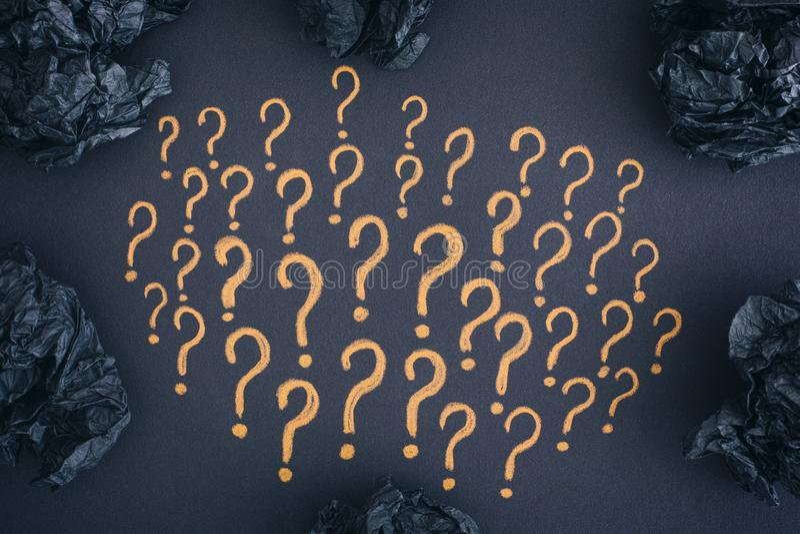 Frågefläckar och svart skrynklade pappers- bollar arkivfoton