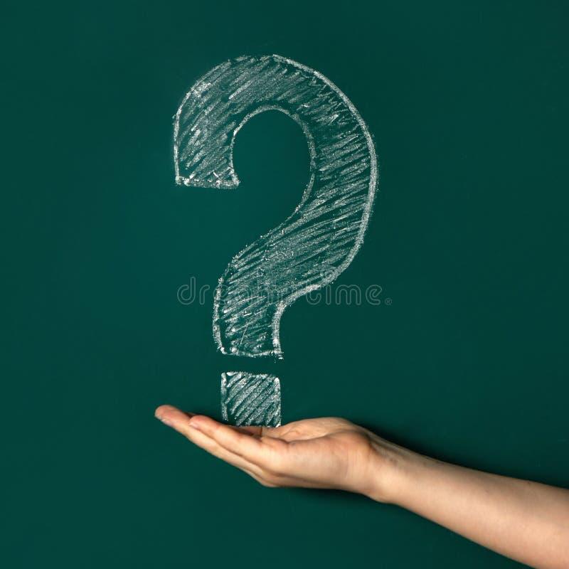 Frågefläcken dras i vit krita på en grön svart tavla kall lokal H?nderna av ett barn royaltyfri foto