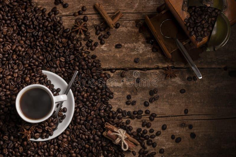 Från den ovannämnda koppen av svart kaffe med bönor och molar på trä arkivbild