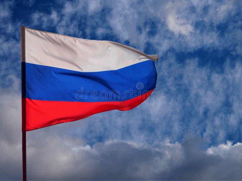 Från den ryska federationen vinka för nationsflagga i vinden på åskmolnen och bakgrunden för blå himmel fotografering för bildbyråer