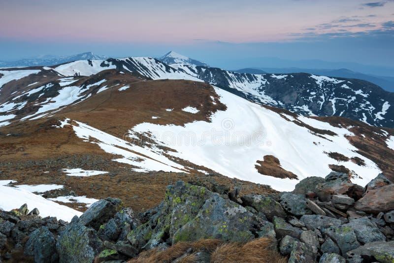 Från gräsmattan öppnar en panoramautsikt av bergen med snö täckte hackor som är upplyst vid morgonsolstrålarna Soluppgång arkivfoton