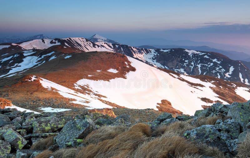 Från gräsmattan öppnar en panoramautsikt av bergen med snö täckte hackor som är upplyst vid morgonsolstrålarna Soluppgång fotografering för bildbyråer