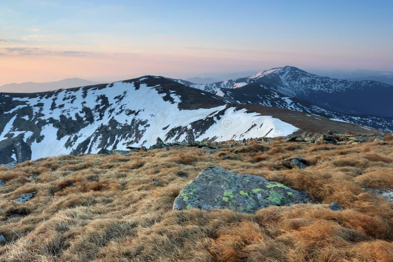 Från gräsmattan öppnar en panoramautsikt av bergen med snö täckte hackor som är upplyst vid morgonsolstrålarna Soluppgång arkivbild