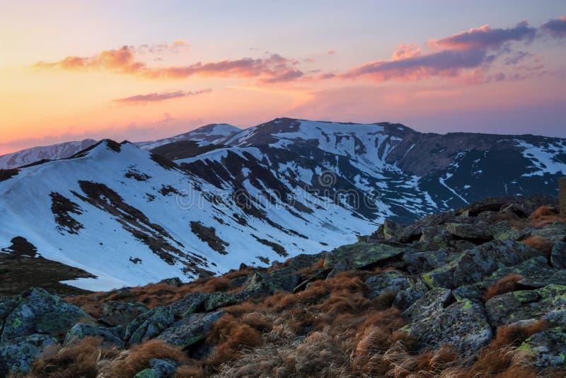 Från gräsmattan öppnar en panoramautsikt av bergen med snö täckte hackor som är upplyst vid morgonsolstrålarna Soluppgång royaltyfria foton
