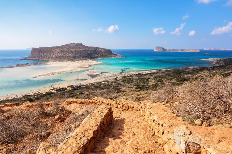 Från momenten öppnar en oerhörd sikt på ett landskap med ett hav av azur färg, en sand och bergstranden Ett förtöjt skepp arkivfoto