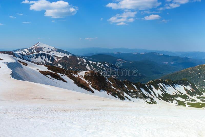 Från snön öppnar täckt gräsmatta en sikt av höga berg med snö täckt blast, blå himmel Storartat vårlandskap royaltyfri bild