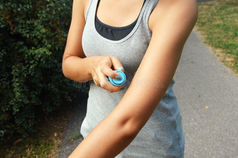 Frånstötande sprej för mygga Kvinna som besprutar krypimpregneringsmedlet mot feltuggor på armhud som är utomhus- i naturskog gen royaltyfri bild