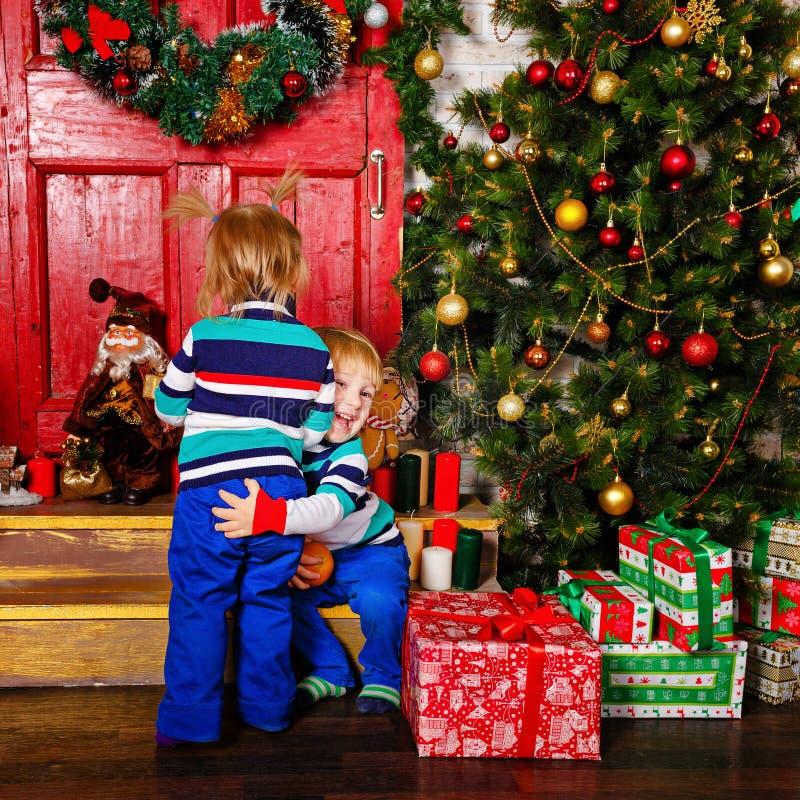 Frère étreignant sa soeur près de l'arbre de Noël photo libre de droits