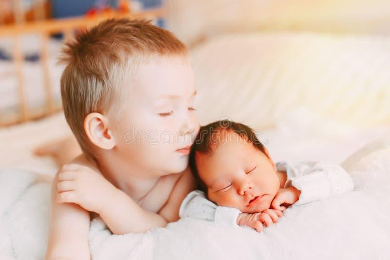 Frère aîné et soeur nouveau-née de bébé se trouvant sur le lit à la maison photographie stock libre de droits