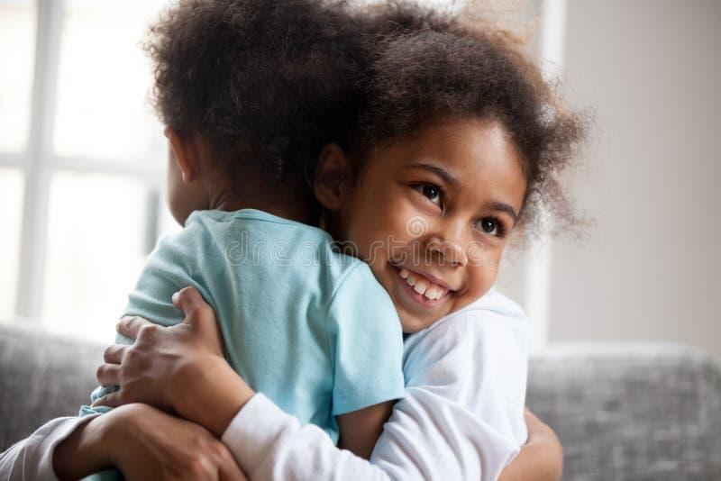 Frère adorable d'étreinte de petite fille d'afro-américain photographie stock
