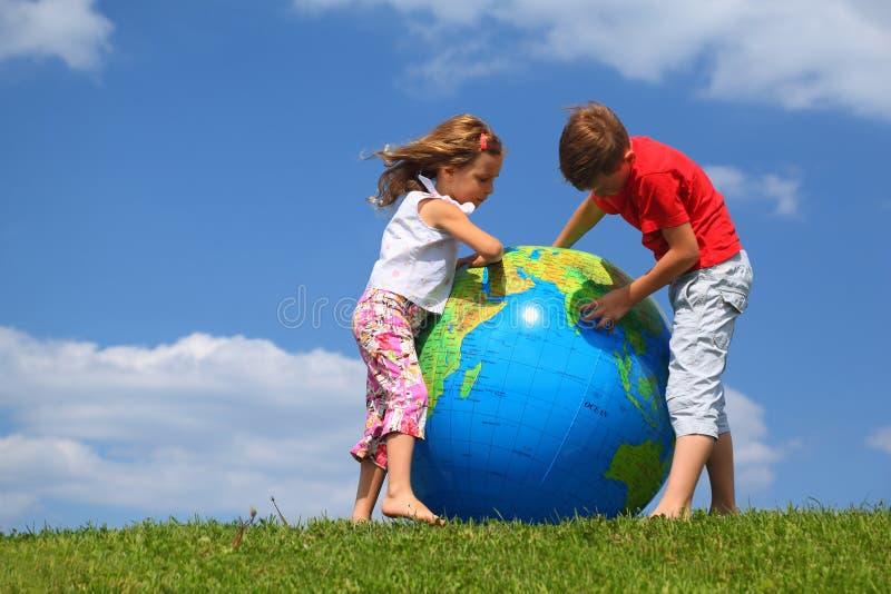 Frère avec la carte d'étude de soeur sur un globe photographie stock libre de droits