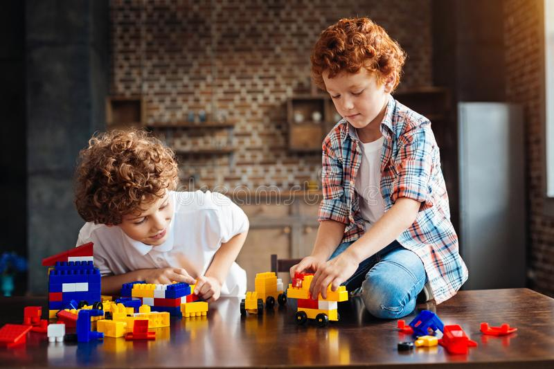 Frère bouclé jouant avec les blocs constitutifs à la maison photo stock