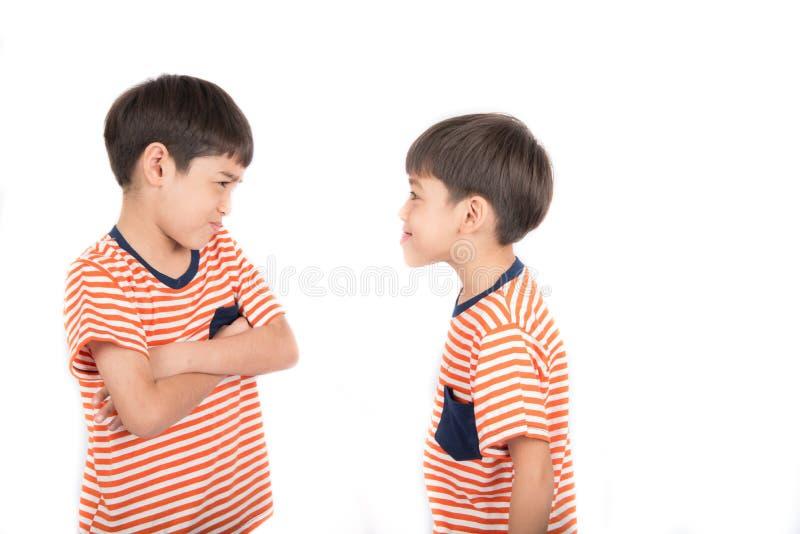 Frère de combat de petit garçon d'enfant de mêmes parents avec mauvaise humeur sur le fond blanc images stock
