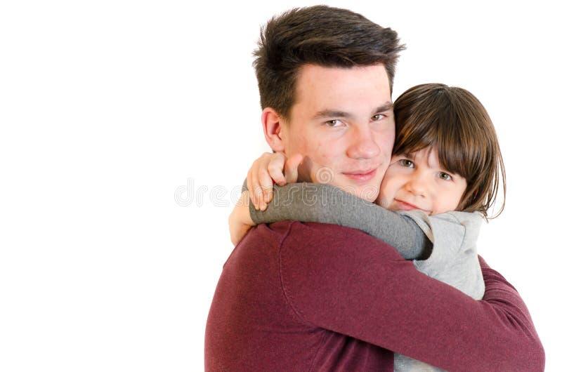 Frère et petite soeur étreignant l'amour qu'a isolé sur le wh photographie stock libre de droits