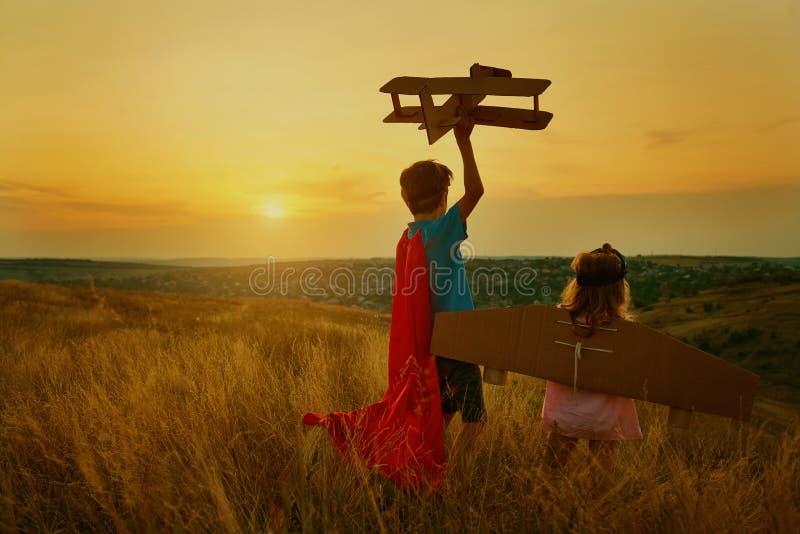 Frère et soeur dans les costumes des pilotes de super héros au coucher du soleil photo libre de droits
