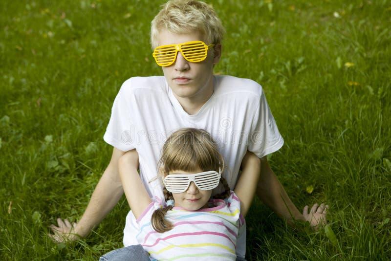Frère et soeur dans se reposer étrange de lunettes de soleil image libre de droits