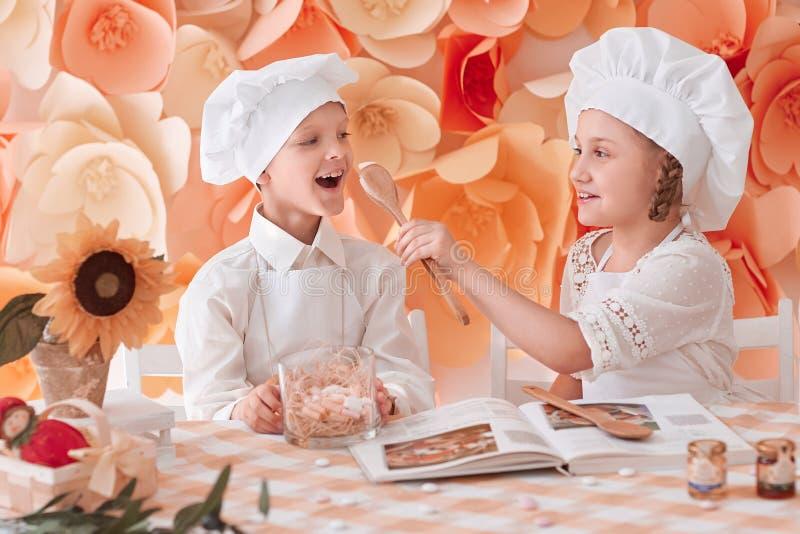 Frère et soeur dans une position uniforme de chef près de la table de cuisine images libres de droits