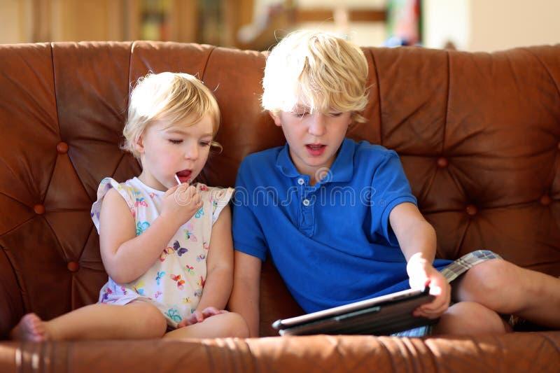 Frère et soeur jouant avec le PC de comprimé à la maison image libre de droits