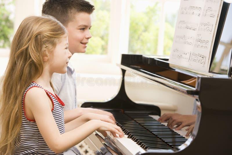 Frère et soeur jouant le piano photo libre de droits