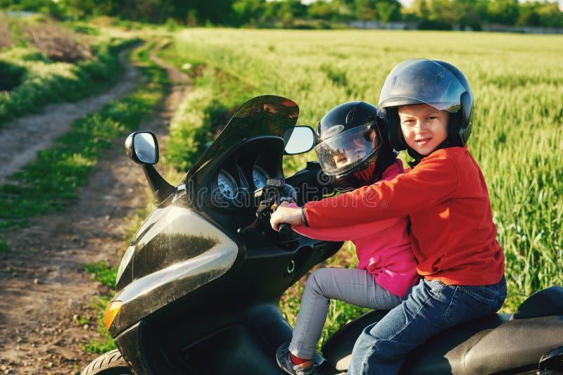 Frère et soeur jouant sur une moto image libre de droits