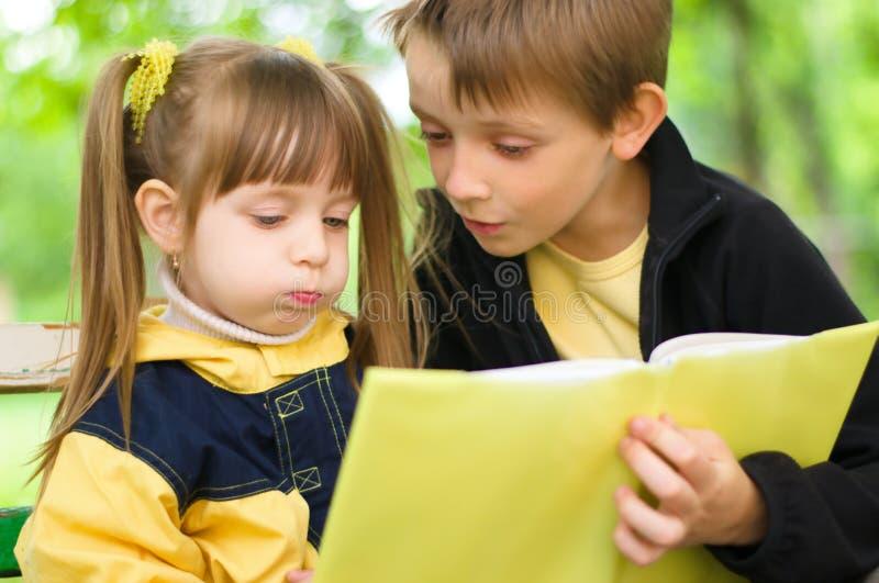 Frère et soeur, lisant un livre photos stock