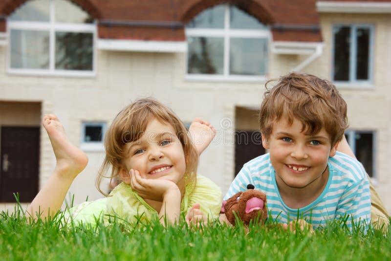 Frère et soeur se trouvant sur la pelouse devant la maison image libre de droits