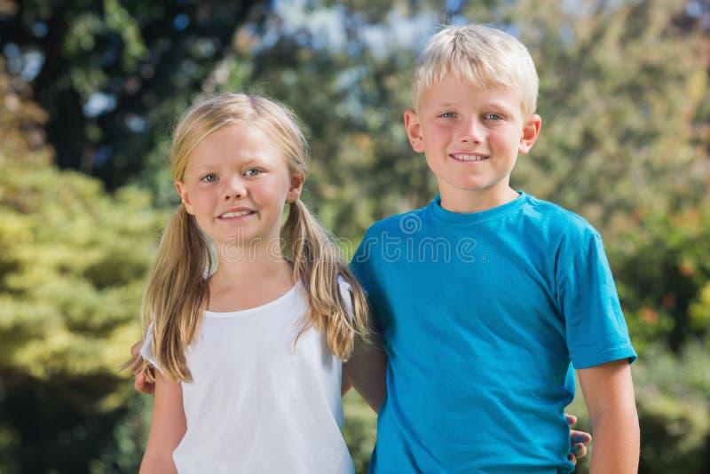 Frère et soeur souriant à l'appareil-photo photo libre de droits