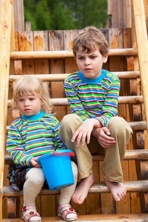 Frère et soeur sur la cour de jeu des enfants photographie stock libre de droits