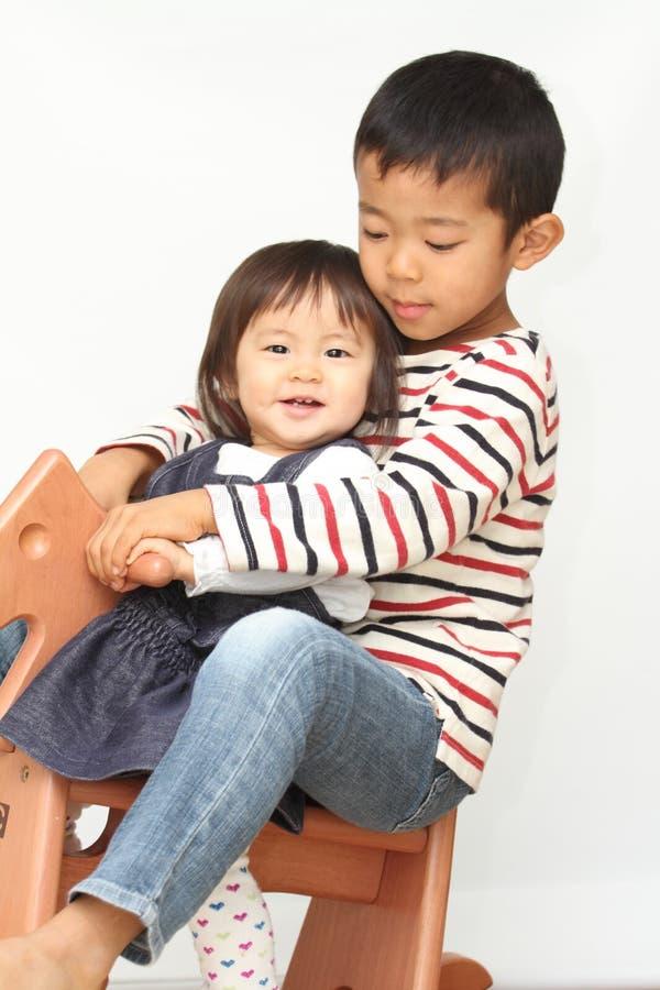 Frère japonais et soeur jouant avec le cheval de basculage images stock