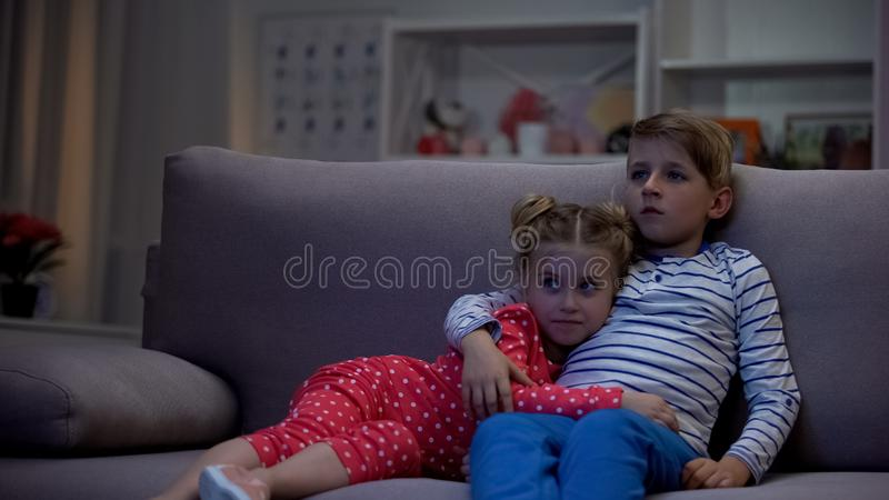 Frère mignon et soeur étreignant, film de observation, loisirs d'instrument, télévision photographie stock