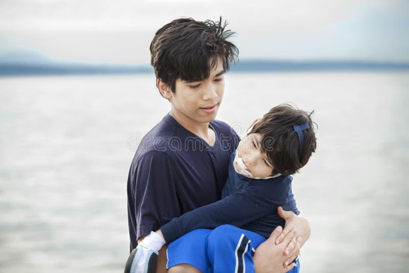 Frère portant le garçon handicapé par le rivage de lac photos libres de droits
